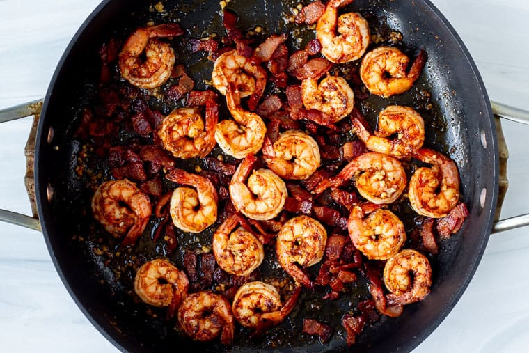 Cajun shrimp and bacon in a black skillet over a white background