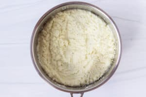 Cauliflower grits cooking in a silver pot over a white background