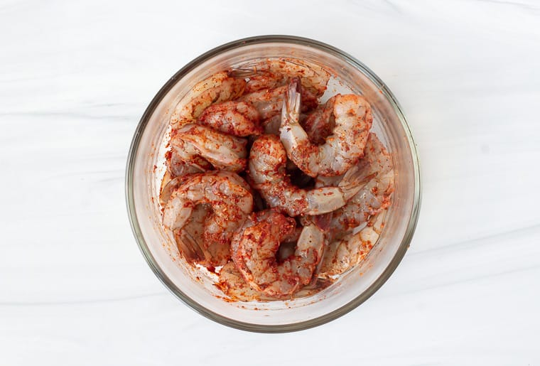 Shrimp tossed in Cajun seasoning in a glass bowl over a white background