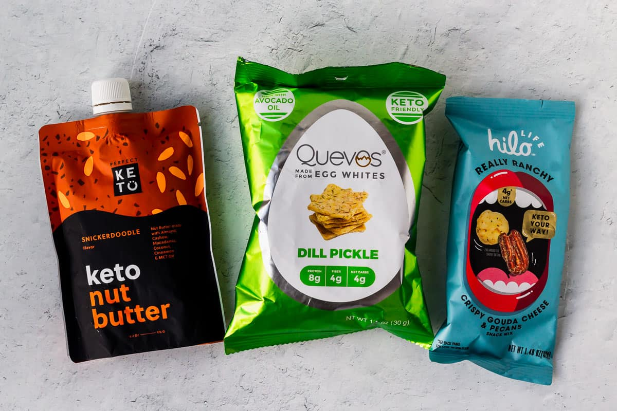 Keto nut butter, quevos, and ranch snacks on a white background