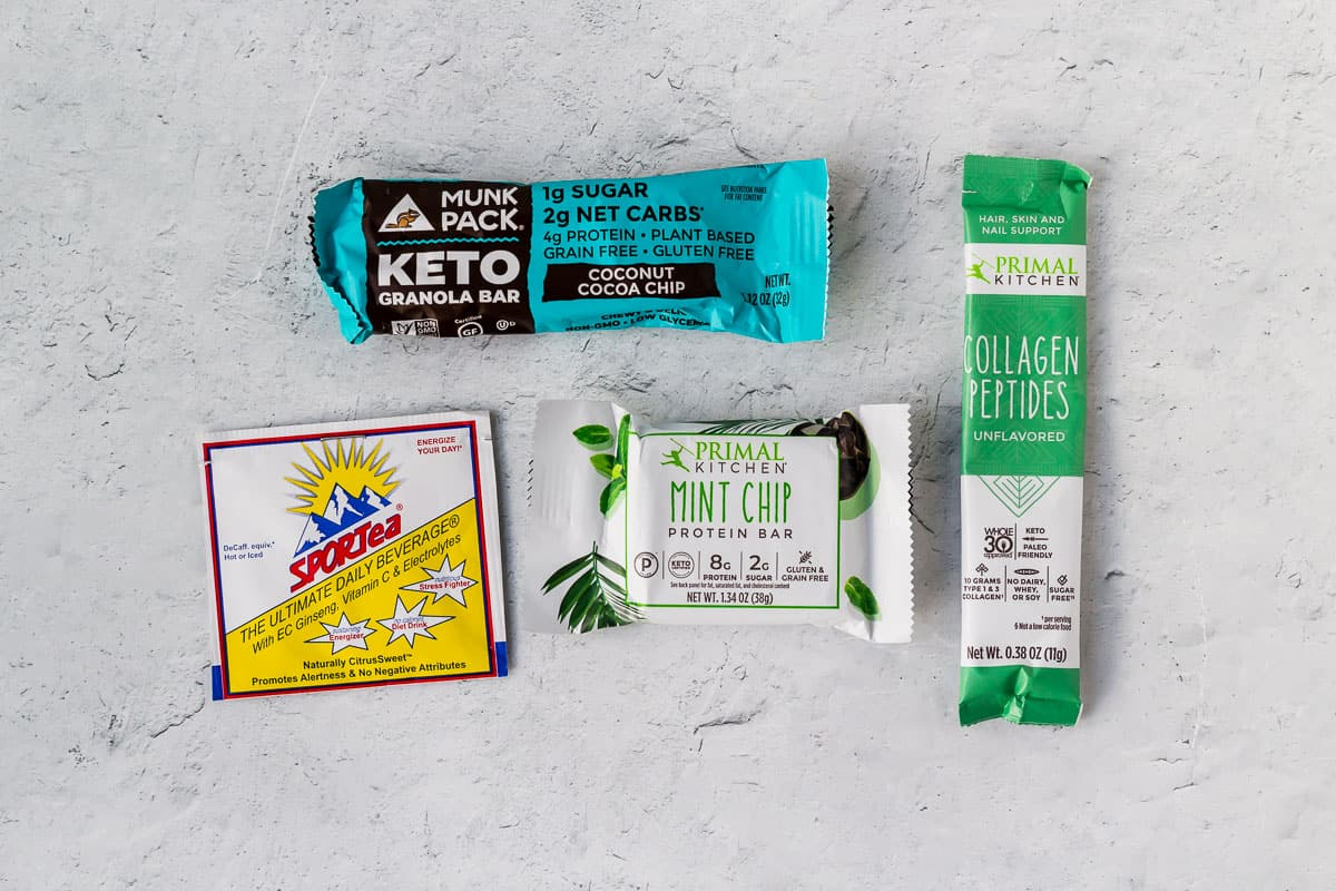 2 keto bars, a pack of collagen, and a tea sample on a white background