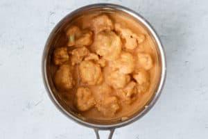 Cauliflower florets in cheese sauce in a saucepan