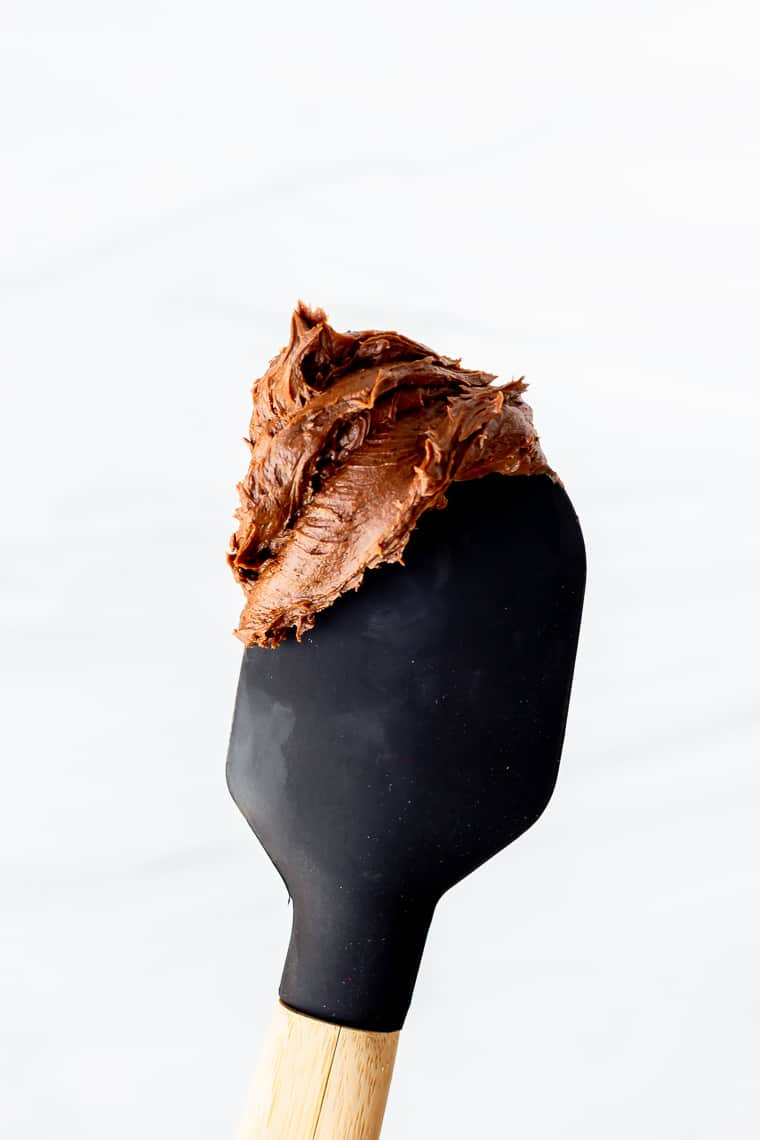 Homemade chocolate buttercream frosting on the tip of a spatula over a white background