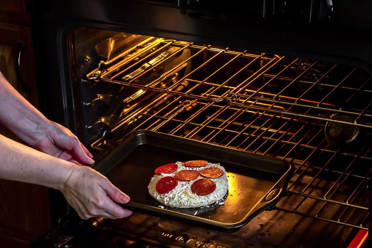 Placing a sheet pan with a small pizza on it in the oven