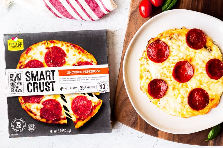 A Poster Farms Smart Crust Uncured Pepperoni Pizza on a plate next to the packaging