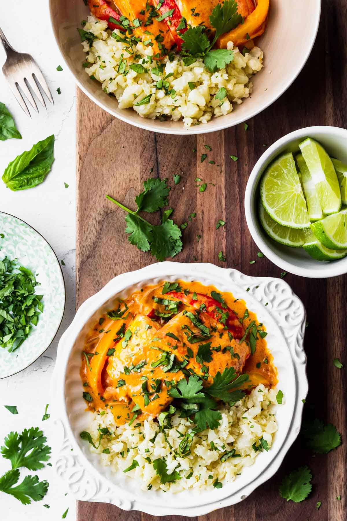 Overhead view of two bowls of cauliflower rice and red curry salmon on a wood board with herbs and limes around it