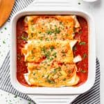 Baked cheesy chicken enchiladas in a white, square baking dish with a striped towel and server next to it