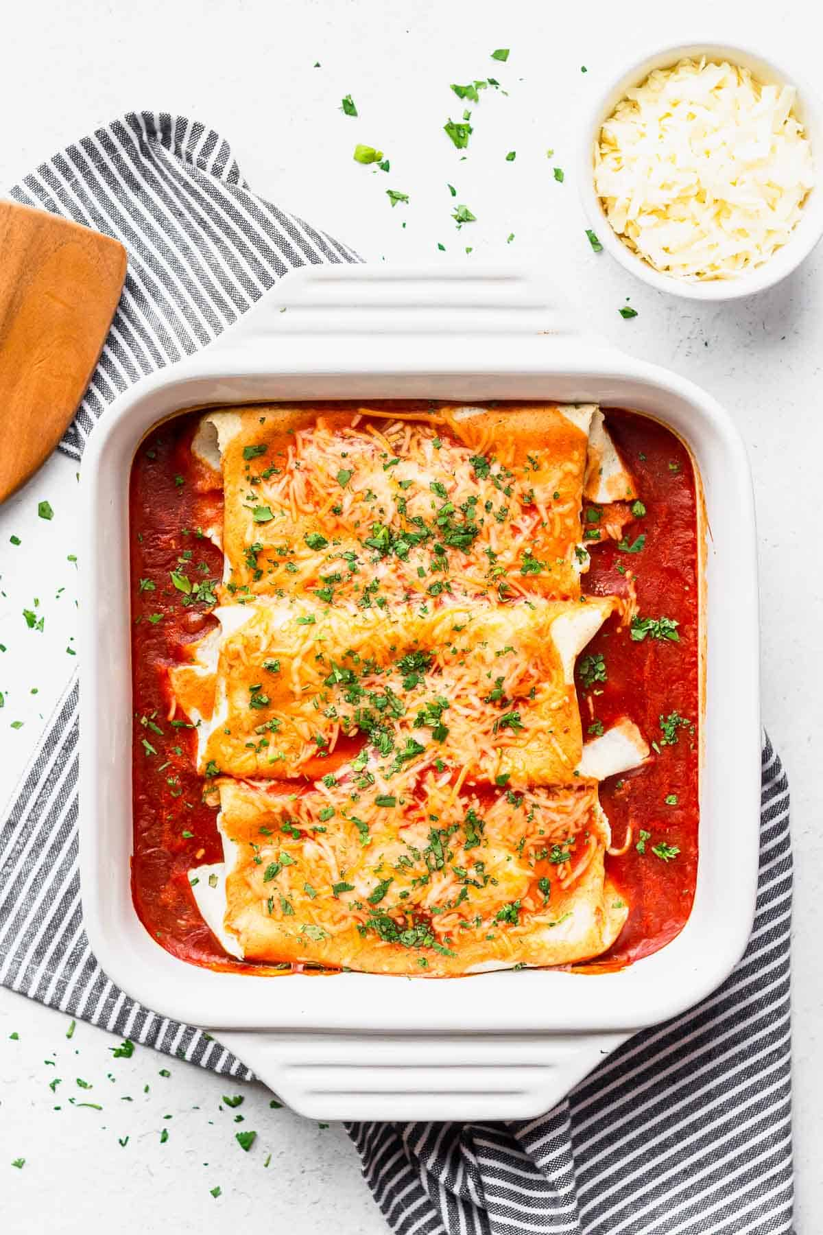 Baked cheesy chicken enchiladas in a white, square baking dish with a striped towel, bowl of shredded cheese, and server next to it