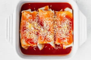 Enchiladas in a baking dish with cheese on top before baking