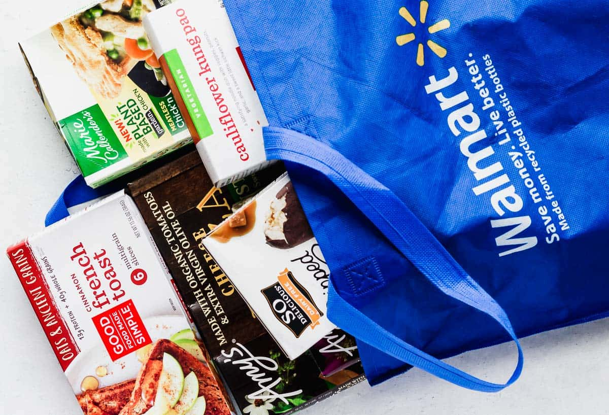 Walmart grocery bag with a variety of plant based frozen meals and foods coming out of it