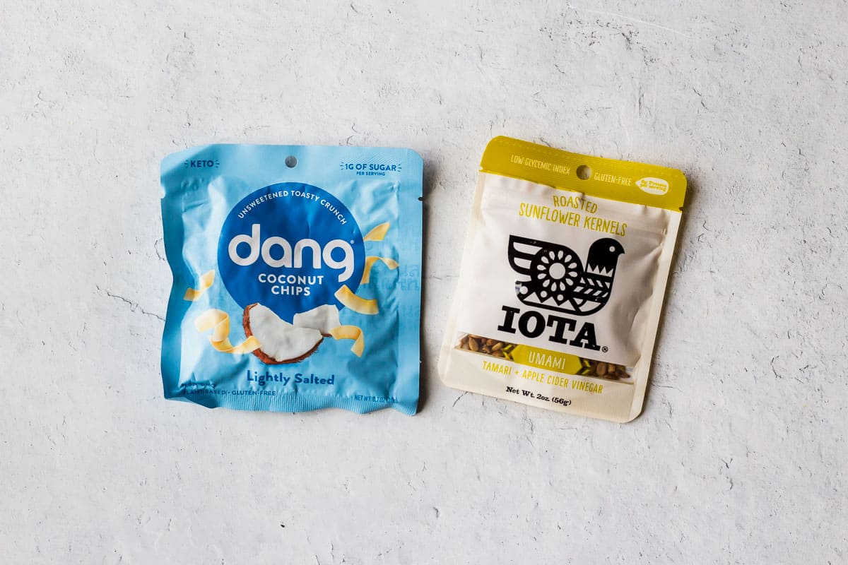 Dang coconut chips package and iota sunflower seeds on a white background