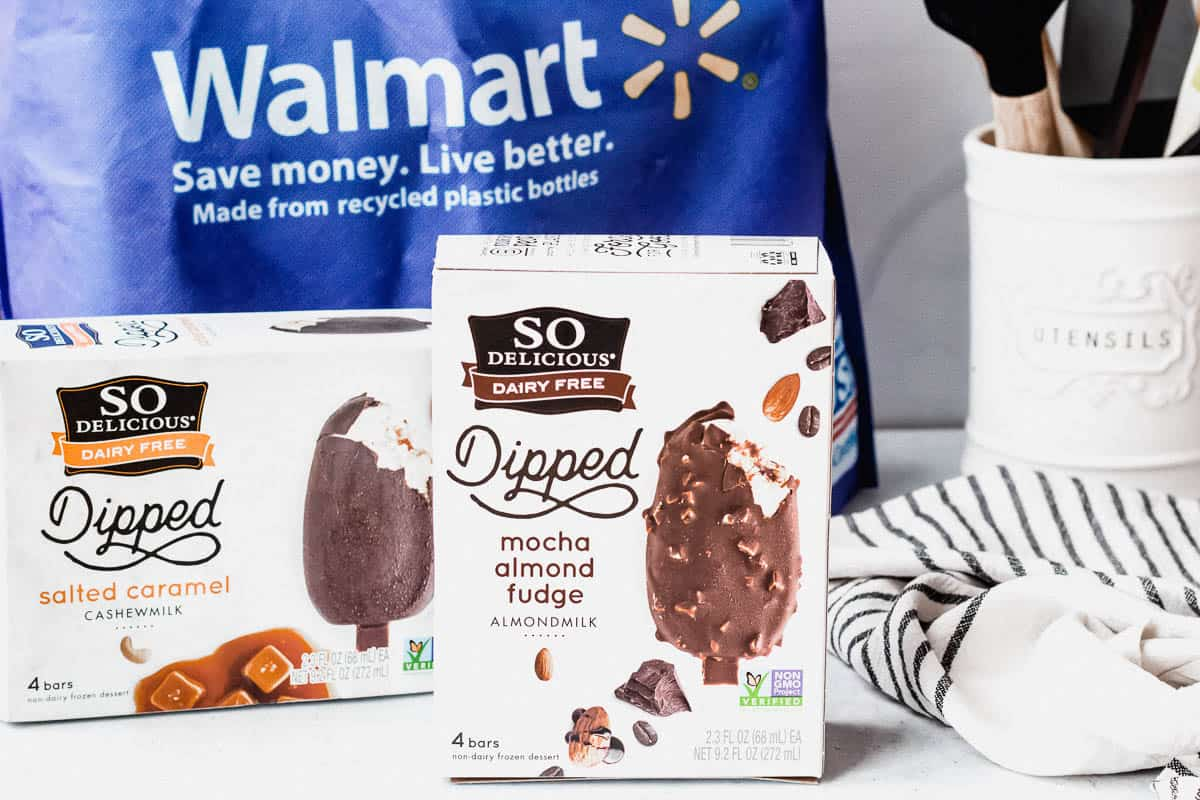 2 boxes of so delicious dairy free ice cream bars in front of a walmart shopping bag with a utensils container and towel near it