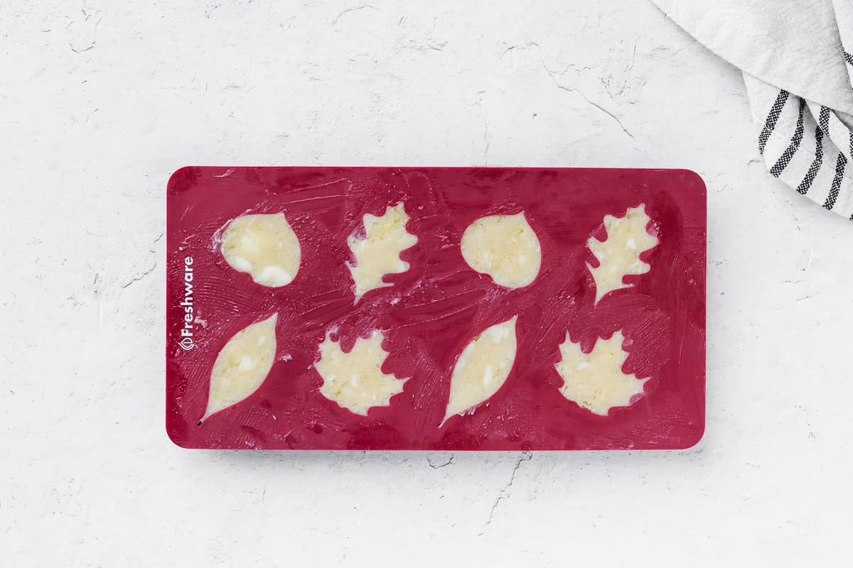 Compound butter pressed into a silicone candy mold on a white background