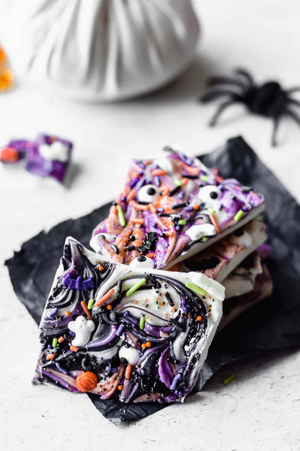 Halloween bark pieces stacked on top of each other with one piece tilted in front, a small white pumpkin and a black toy spider in the background
