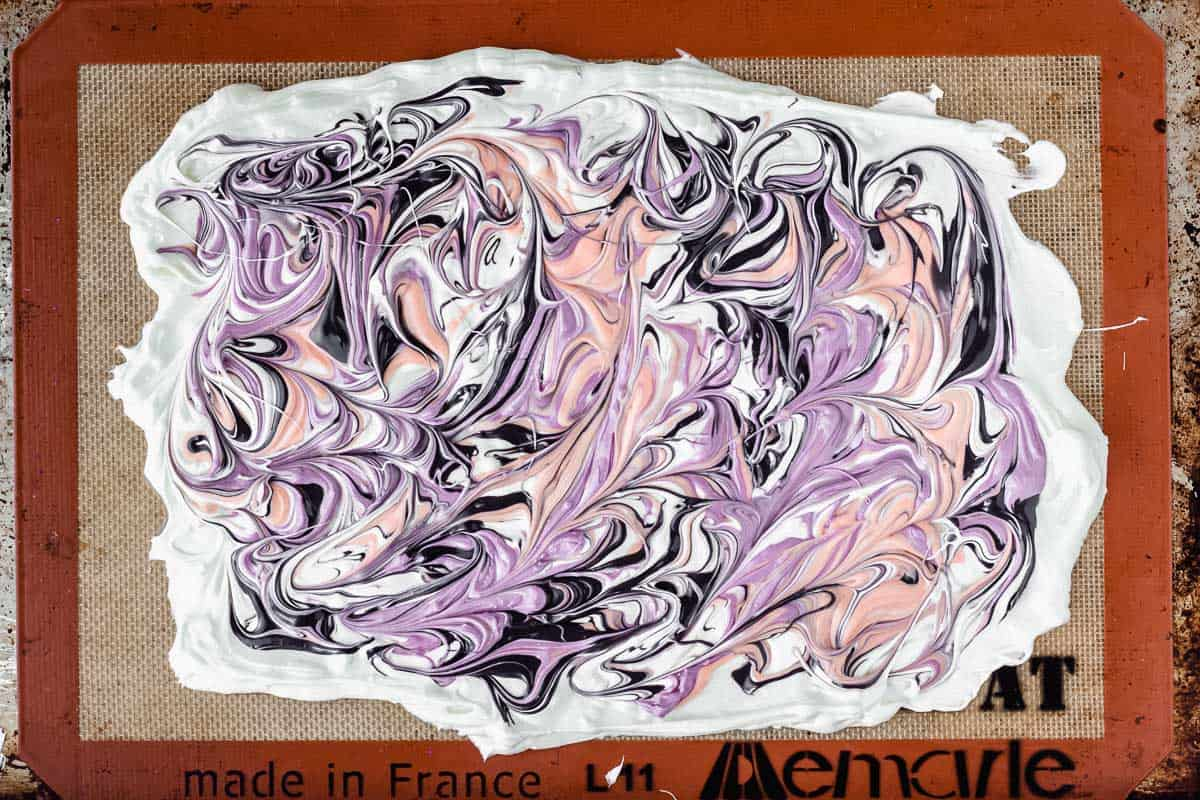 White chocolate spread out with swirls of orange, purple, and black in it.