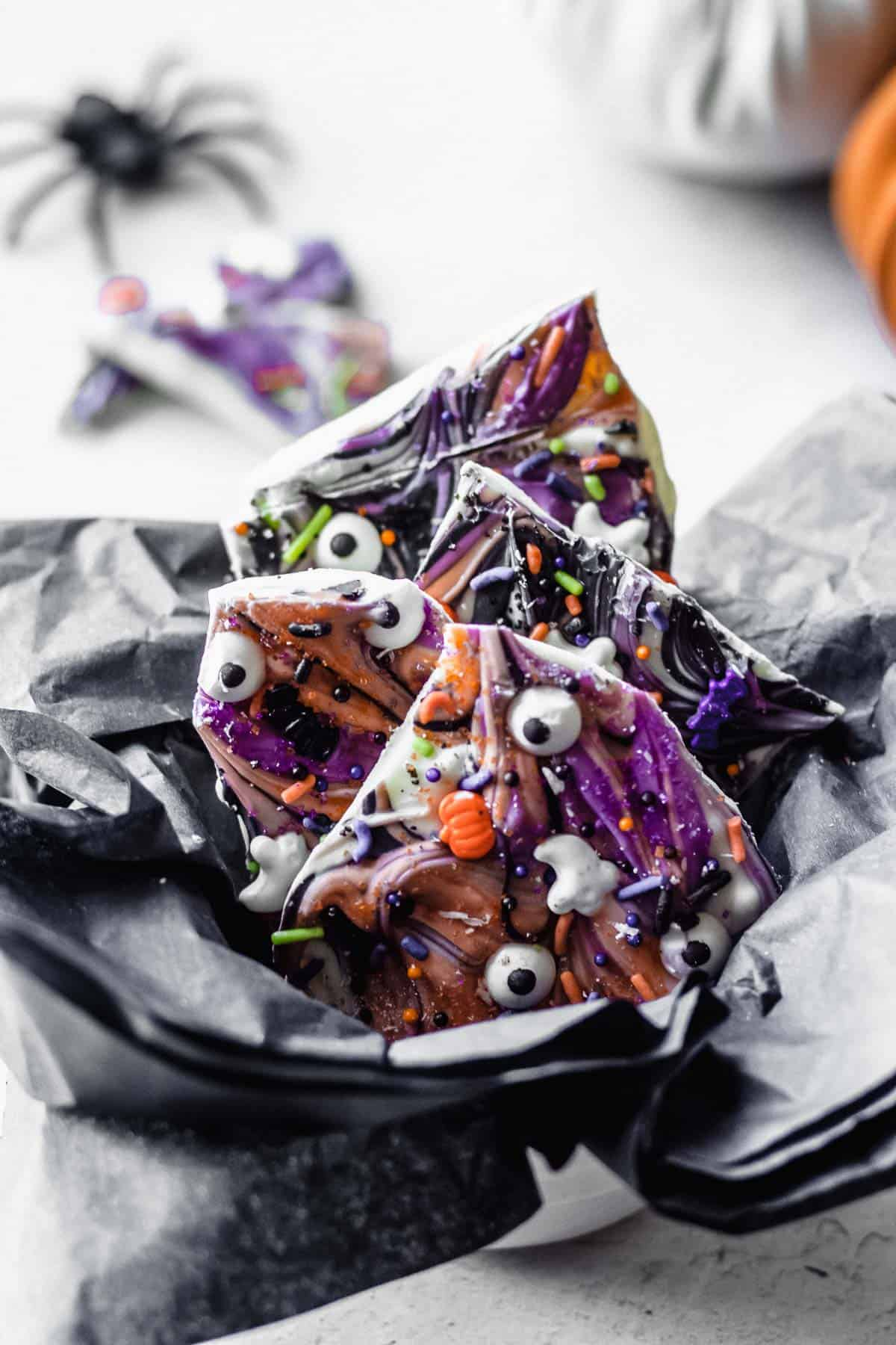 Halloween bark pieces in a white bowl with black tissue paper with a fake spider, white pumpkin, and smaller pieces of candy in the background