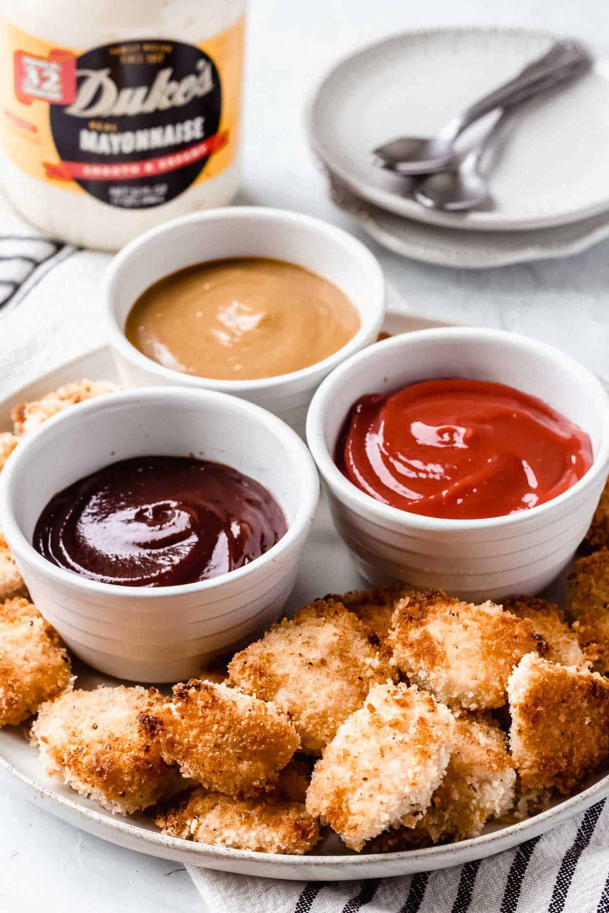 A plate of homemade chicken nuggets and dipping sauce with small plates, spoons, and Duke's mayonnaise in the background