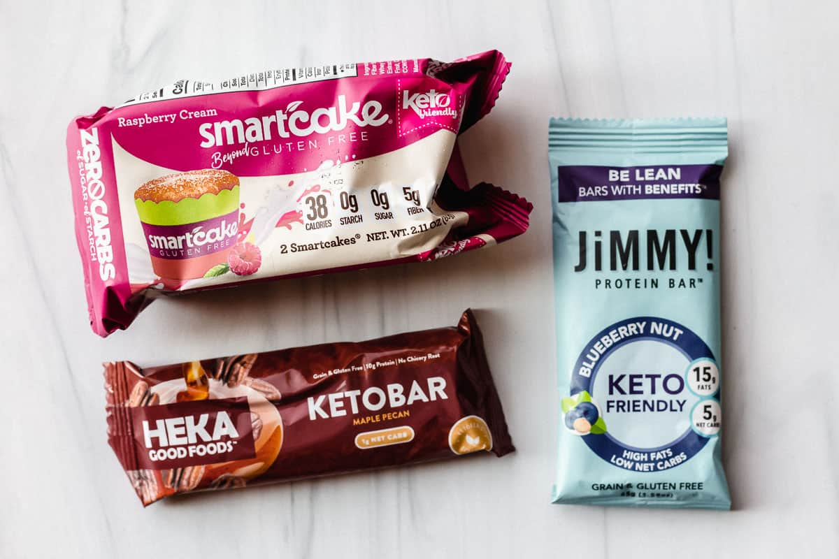 A heka goodfoods bar, a jimmy bar, and a pack of smartcakes on a white background