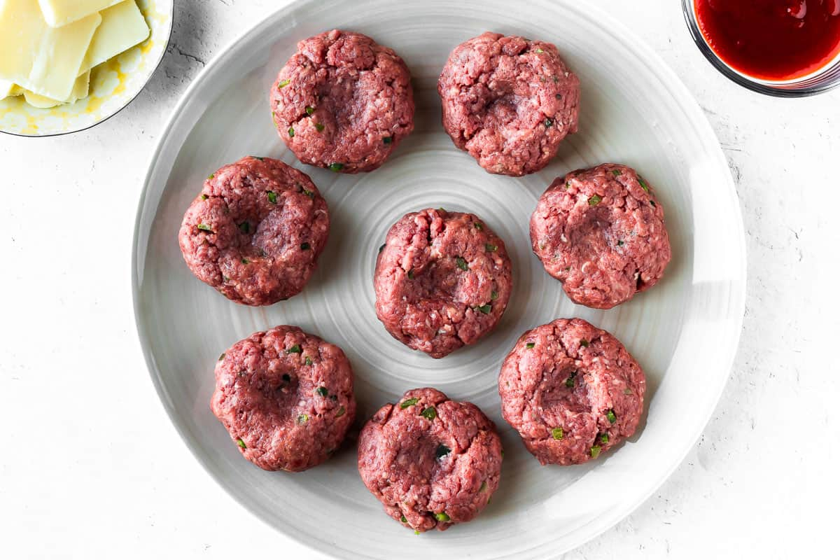8 beef slider patties on a plate on a white background