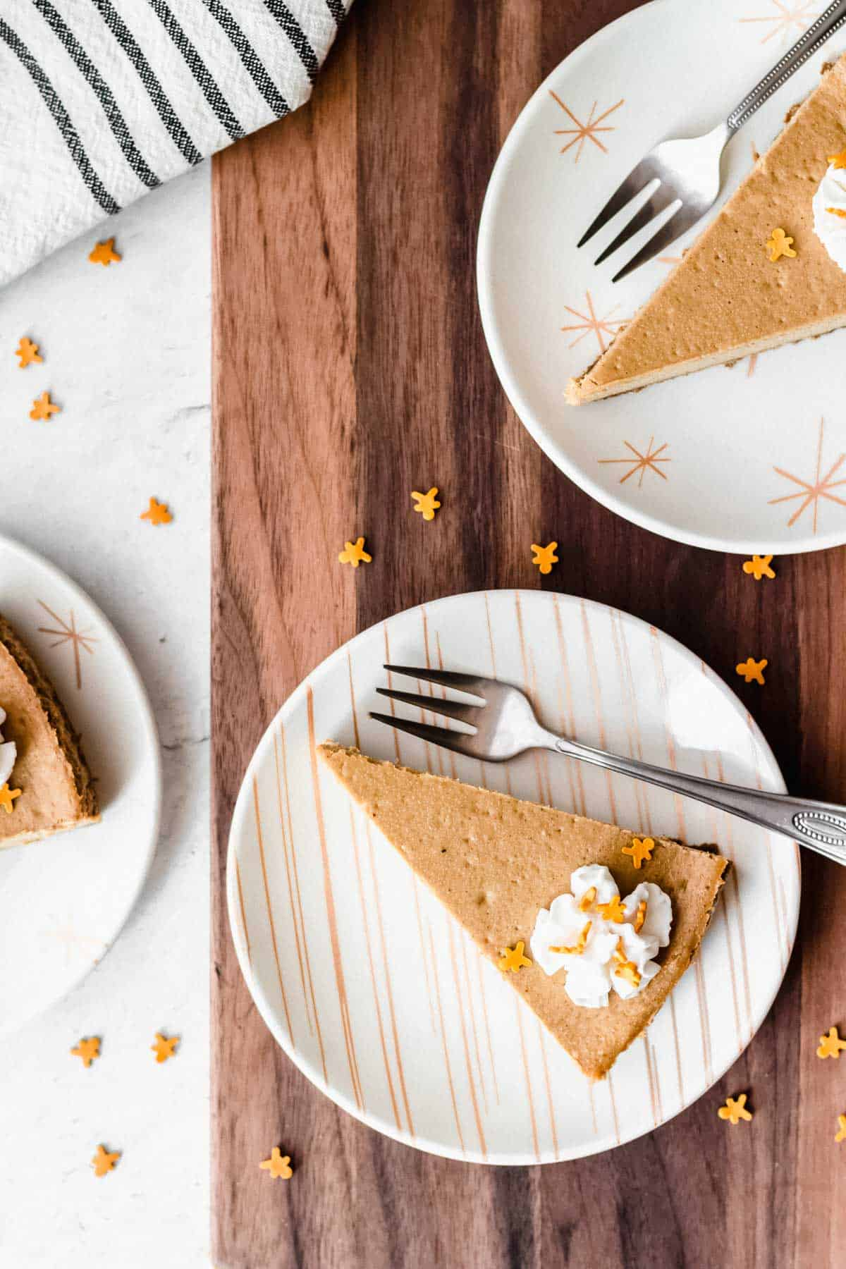 Gingerbread cheesecake slices on small white and gold plates with small forms on a wood board and white background with gingerbread sprinkles around them