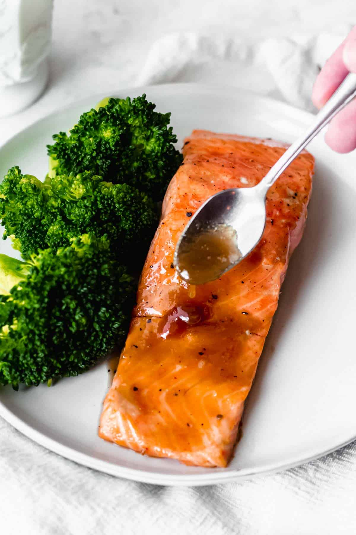 A filet of salmon with maple bourbon glaze being spooned over it on a white plate with broccoli