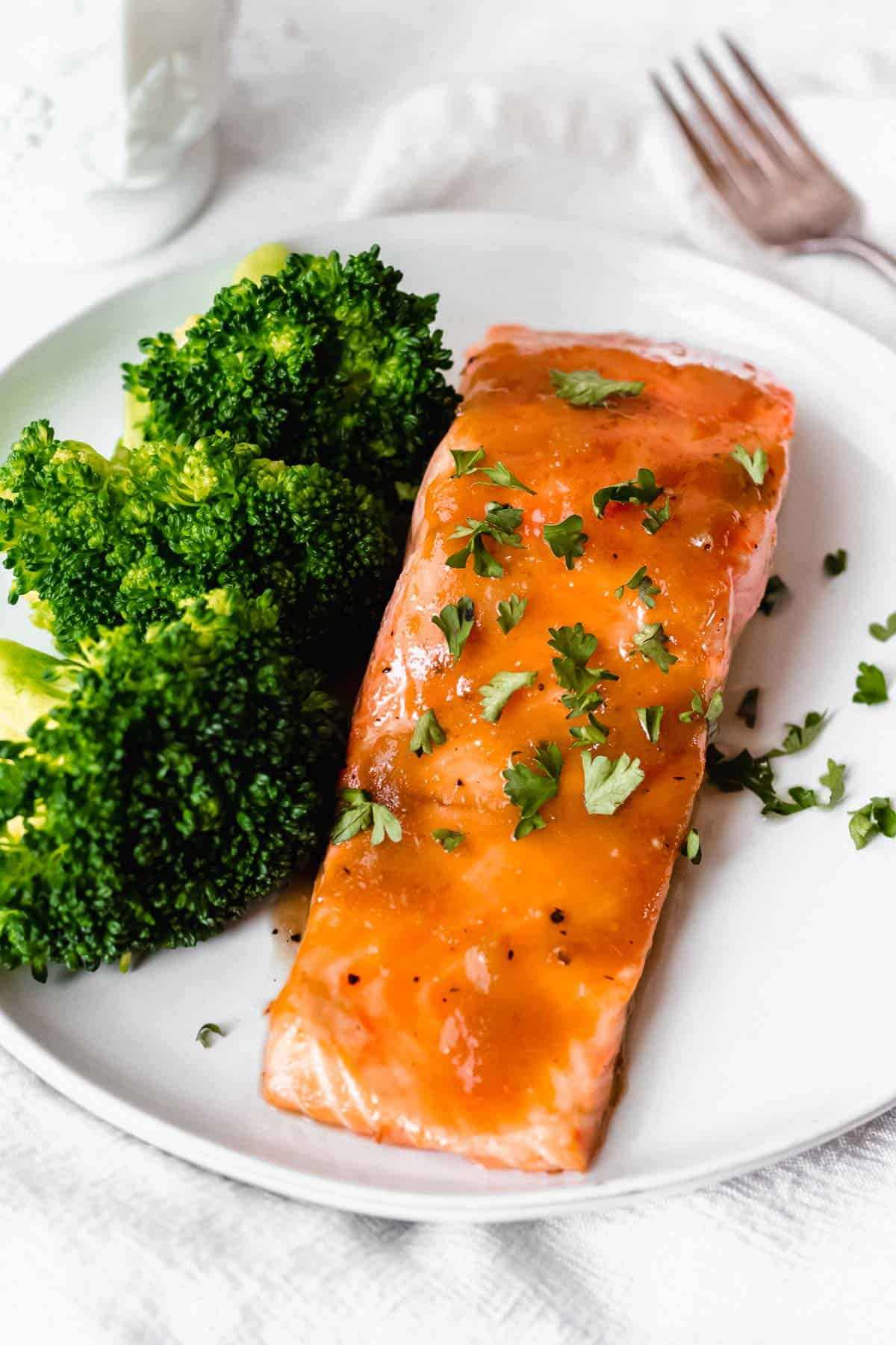 Maple bourbon salmon filet and broccoli on a white plate with a fork and white cup in the background