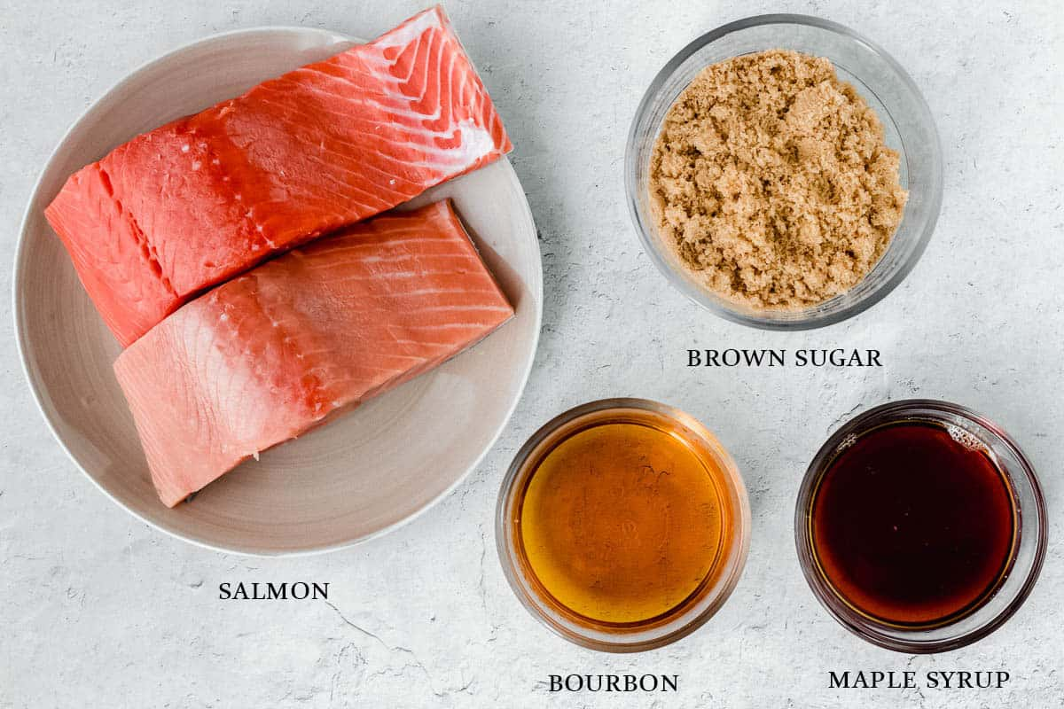 Ingredients needed to. make maple bourbon salmon on a white background with labels