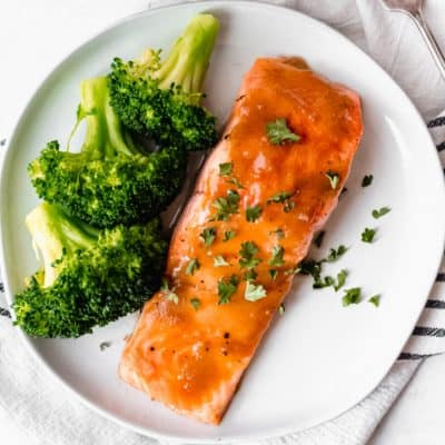 Maple bourbon salmon filet and broccoli on a white plate