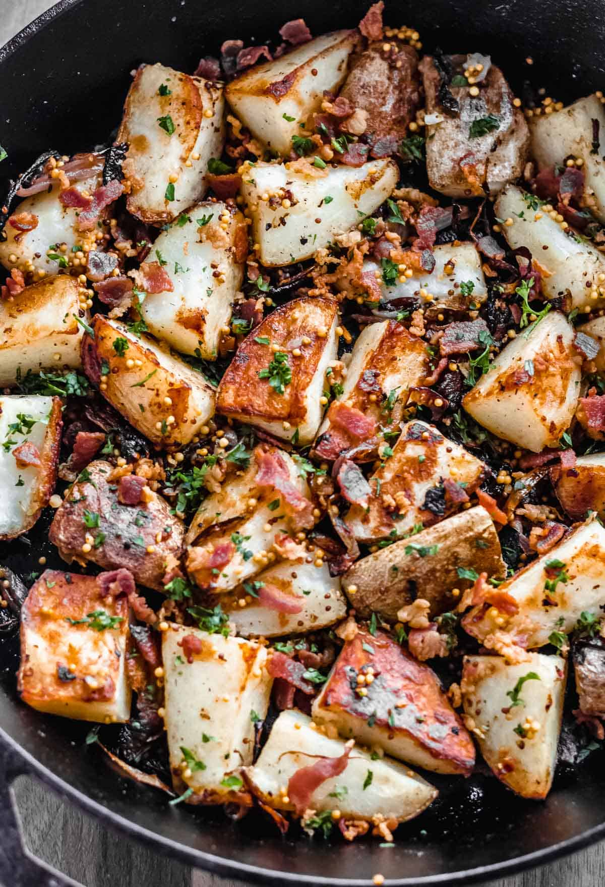 Close up of bacon roasted potatoes with caramelized shallots and parsley
