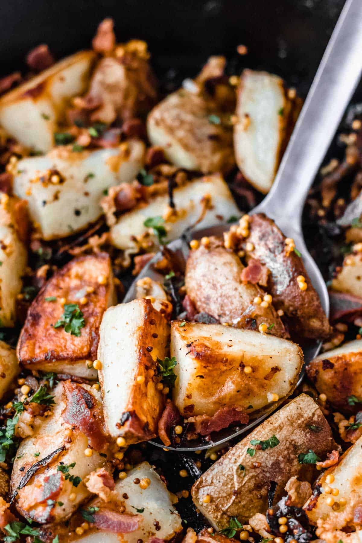 CLose up of a silver spoon with bacon roasted potatoes, caramelized shallots, mustard and parsley