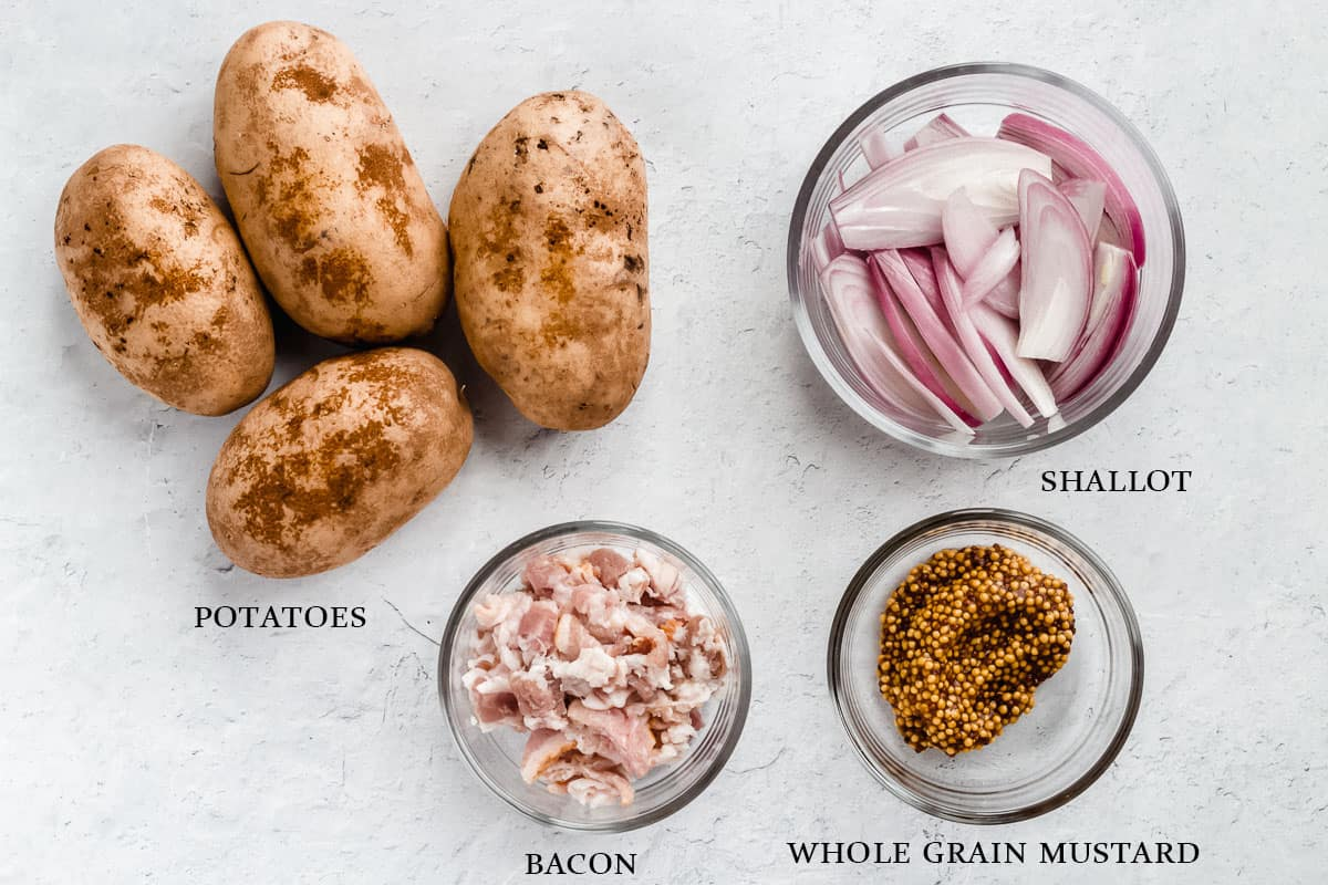 Ingredients for bacon roasted potatoes on a white background with labels