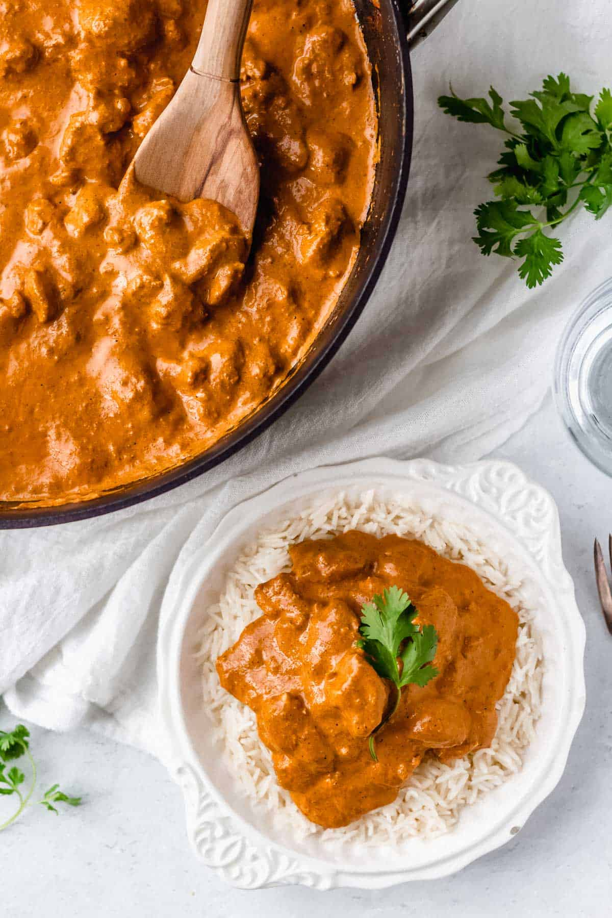 Overhead of butter chicken and rice in a white bowl with part of a pan showing with more butter chicken in it and a wood spoon with a white linen between the pan and bowl and fresh cilantro in the background