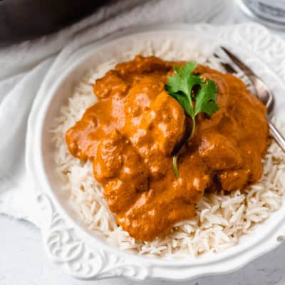 Butter chicken on a bed of white rice in a white bowl over a white background