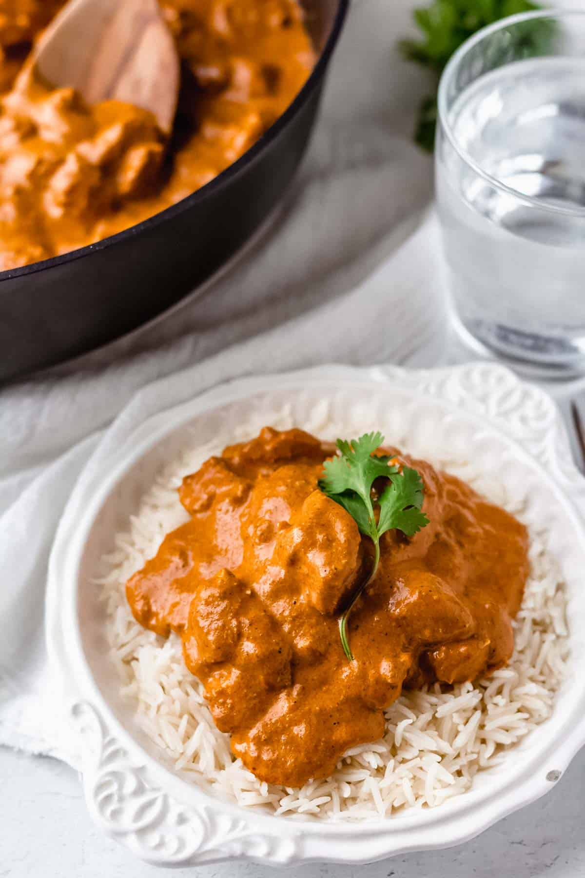 Butter chicken over rice in a white bowl with part of a black pan showing with more butter chicken and a wood spoon inside of it and a glass of water and cilantro next to it