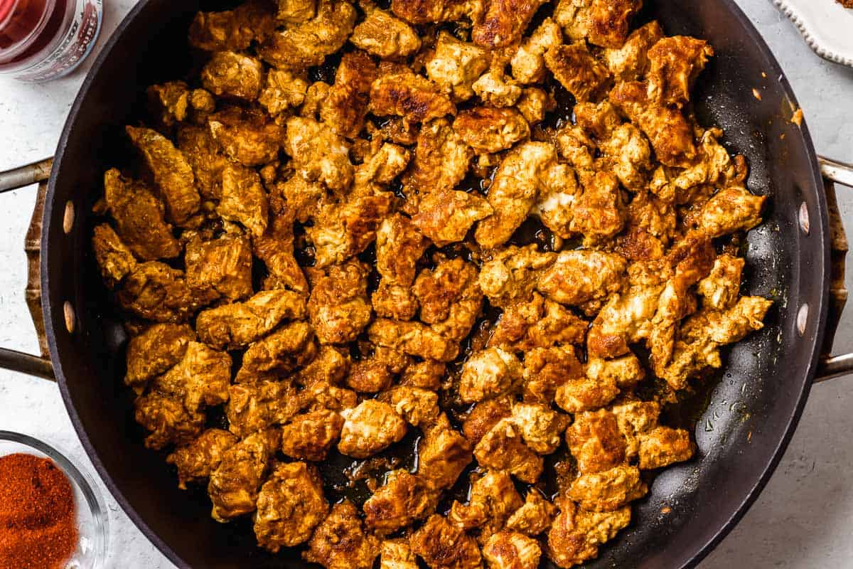 Pieces of spiced chicken cooking in a black skillet