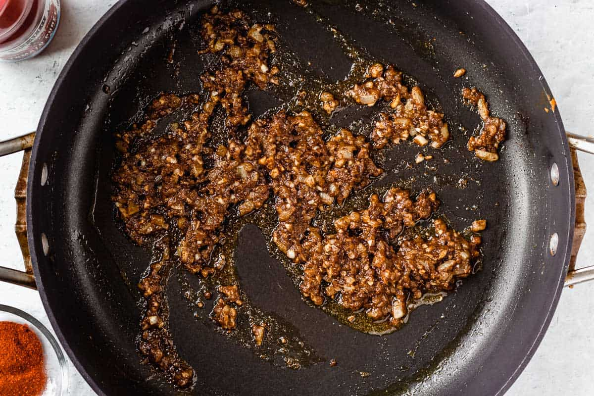 Minced onion, shallot and garlic cooking in butter and spices in a black skillet