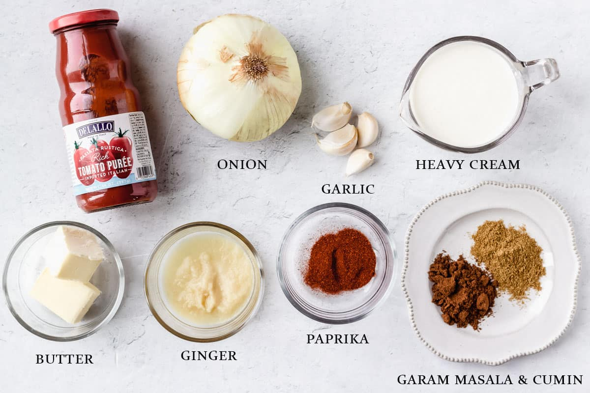 Ingredients needed to make butter chicken gravy or sauce on a white background with labels