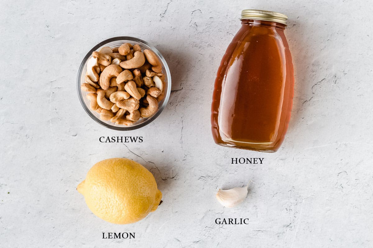 Ingredients to make cashew dip on a white background with labels