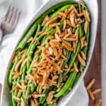 Green beans with almonds in an oblong bowl with text overlay