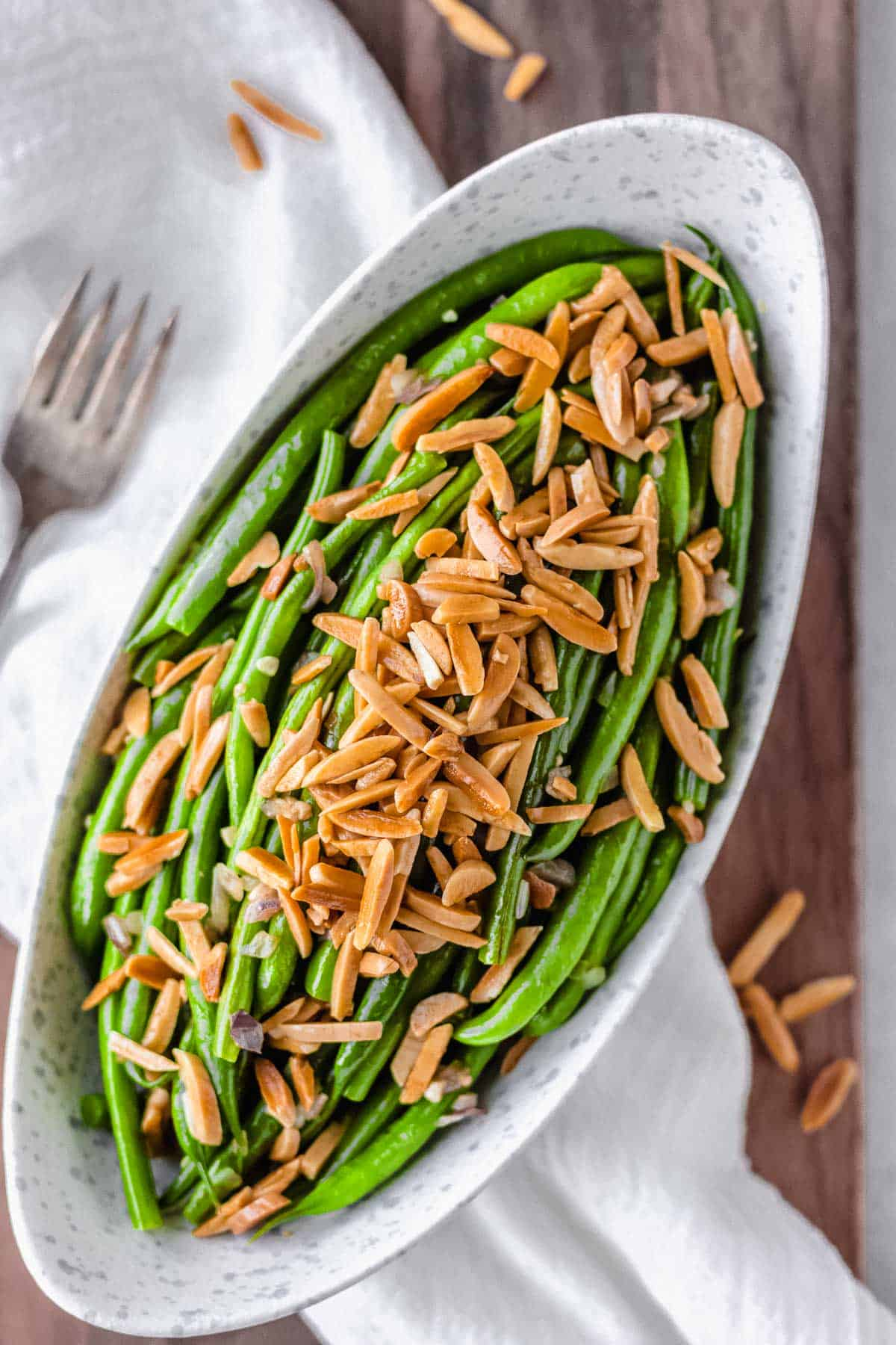 Overhead of an oblong bowl of green beans with almonds over a white napkin and wood board