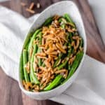 An oblong bowl filled with green beans and almonds over a white towel and wood board