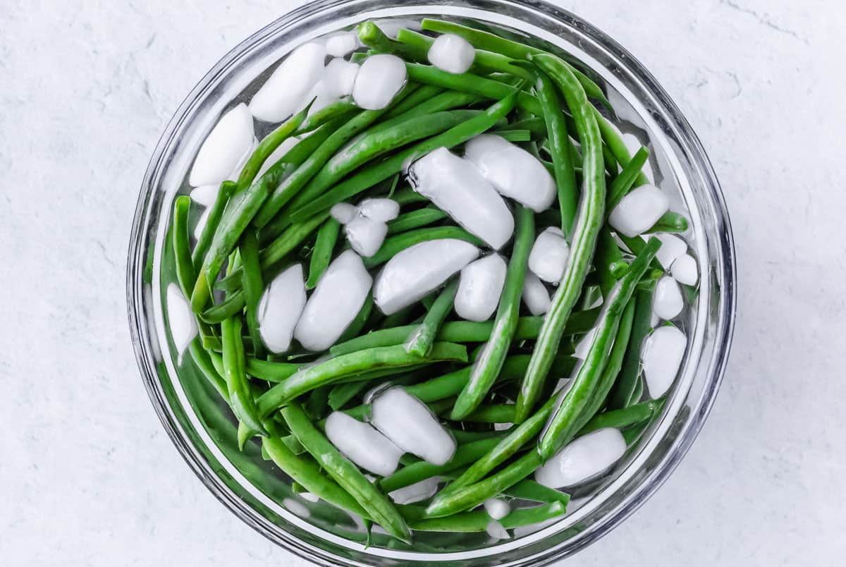 Green beans in a bowl of water with ice over a white background