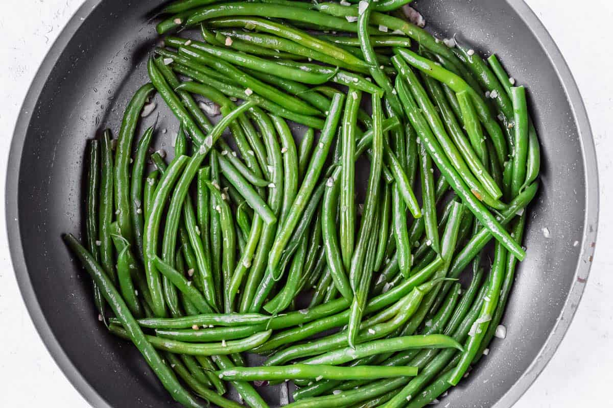 Green beans in a skillet with garlic and shallot