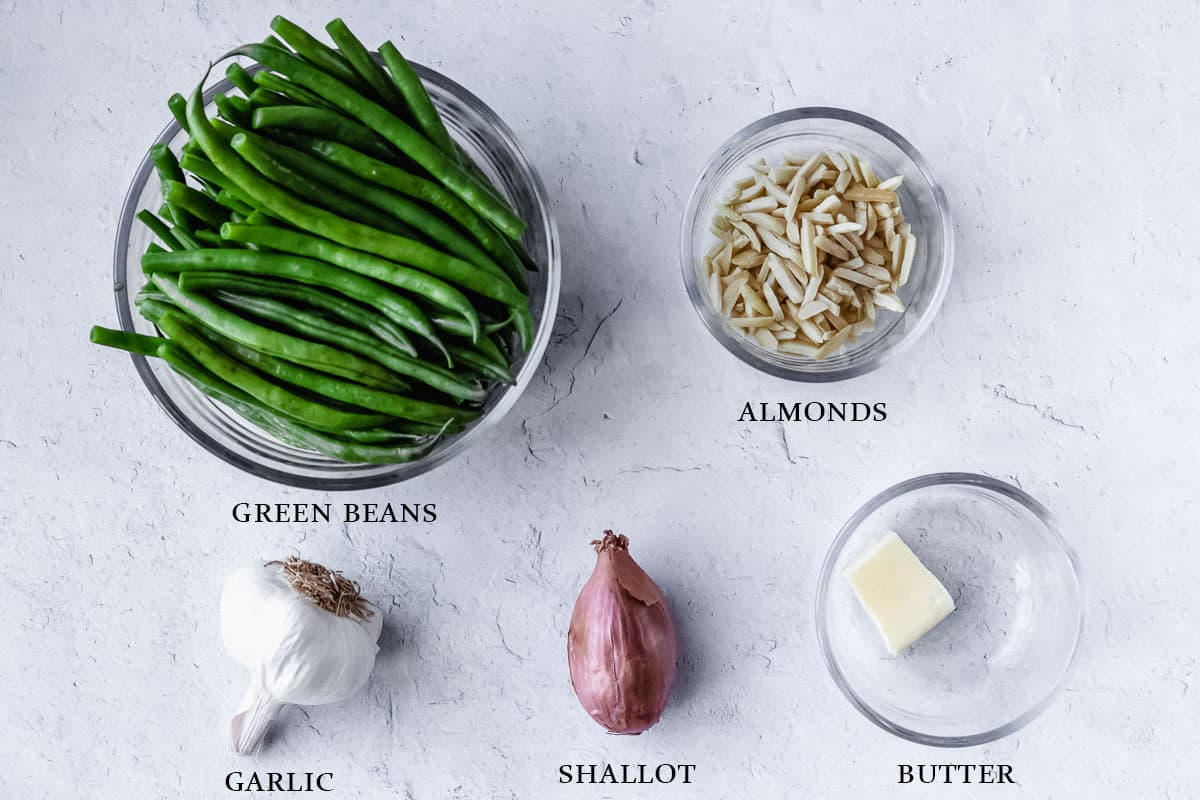 Ingredients to make green beans with almonds on a white background with labels