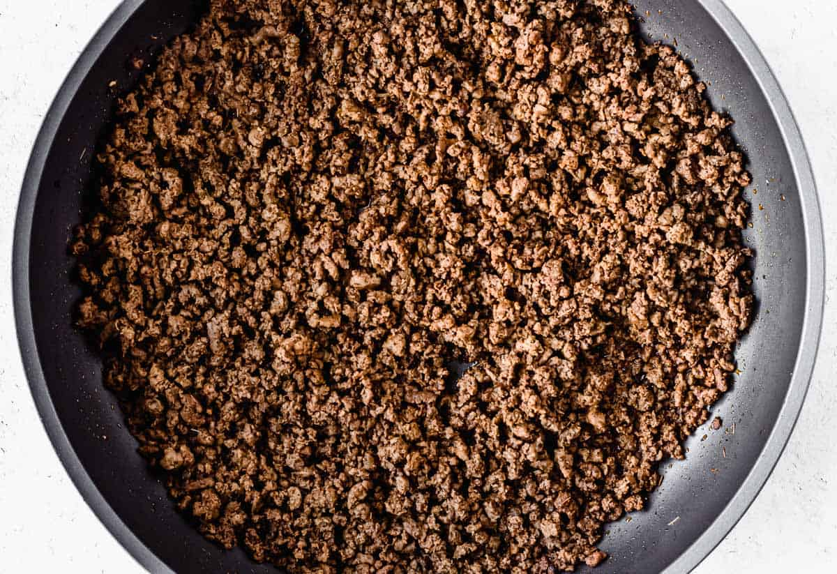 Skillet with seasoned ground beef crumbles in it