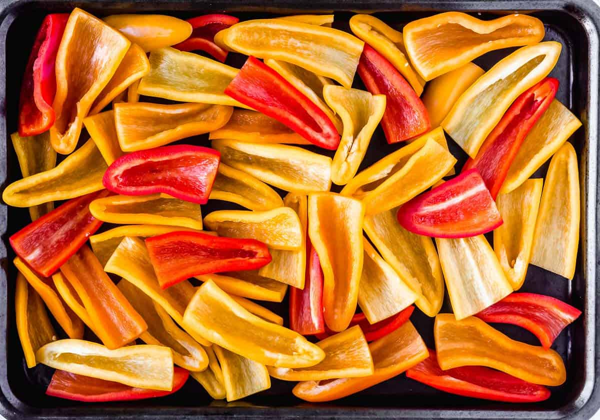 Mini peppers cut in half and spread out onto a baking sheet