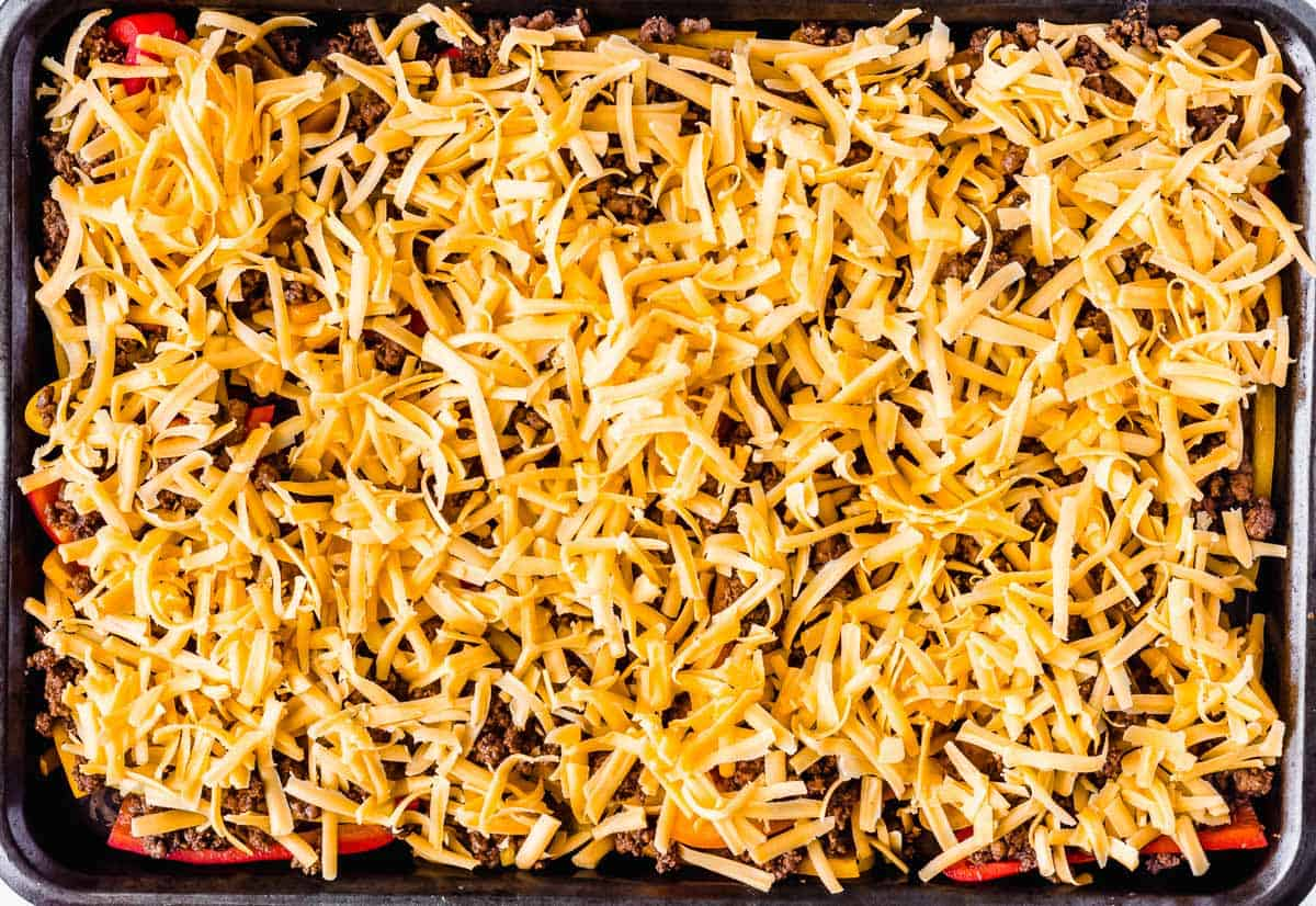 Mini sweet peppers cut in half and topped with ground beef and cheese on a baking sheet