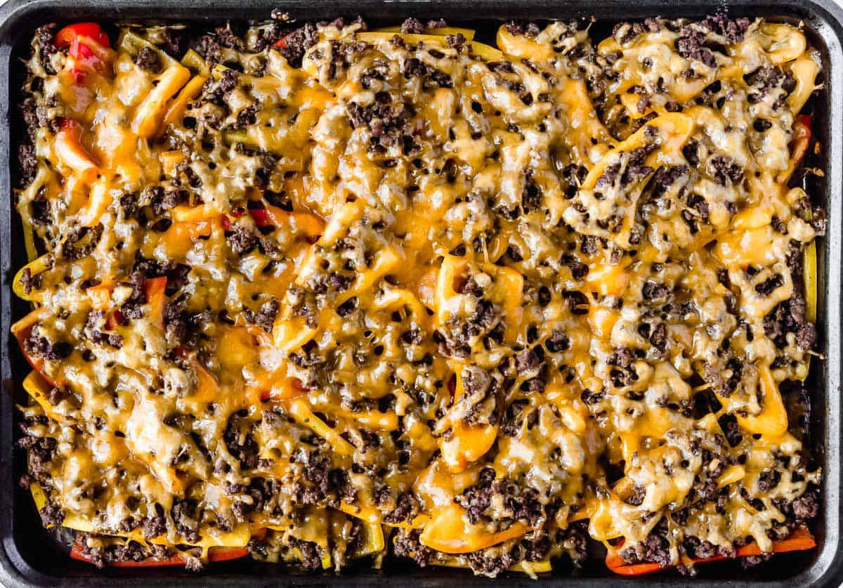 Baked bell pepper nachos with melted cheese on a baking sheet before nacho toppings are added