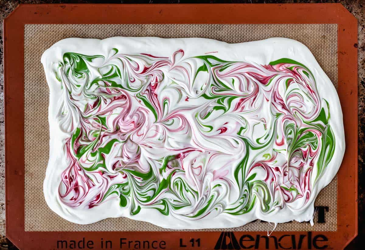 Melted red and green candy melted swirled into melted white chocolate on a silicone baking mat