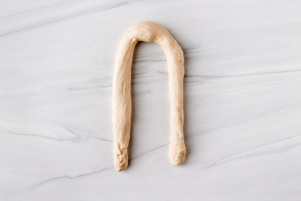 """Pretzel dough rolled in a rope in a """"U"""" shape on a white background"""